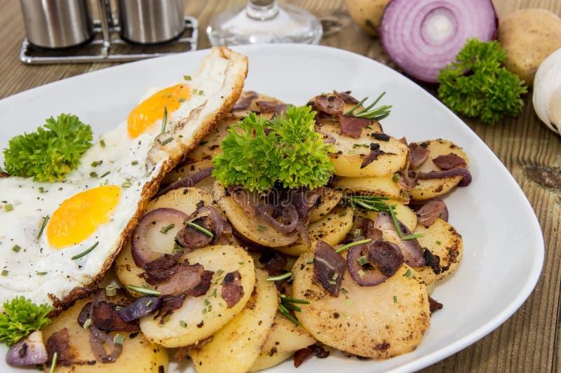 Fried Egg sur un tas des pommes de terre rôties images libres de droits