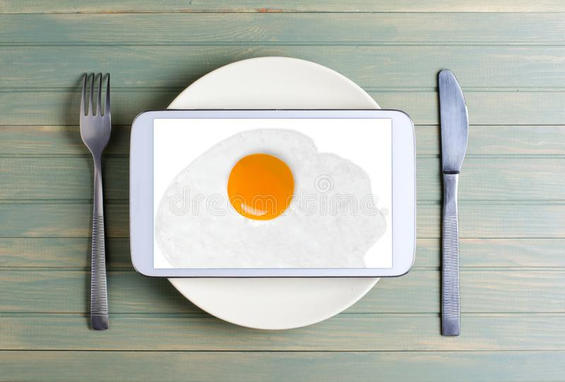Fried egg on the tablet screen. Cutlery - knife and fork. The tablet computer is on a white round plate. Wooden background royalty free stock photography