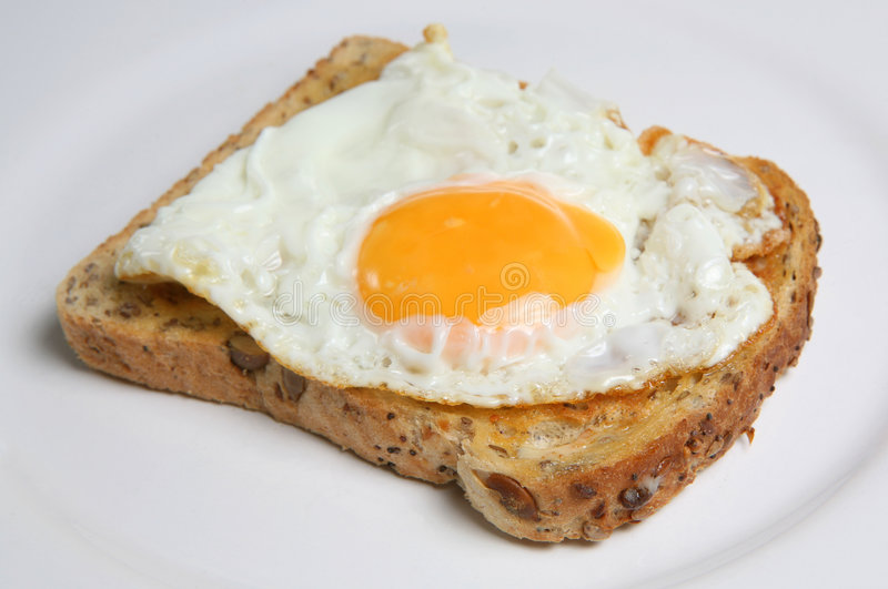 Fried Egg on Toast. Fried free-range egg on wholemeal toast on a white plate stock photography