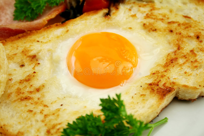 Fried Egg In Toast. Fried egg embedded in toast with bacon and parsley stock photography