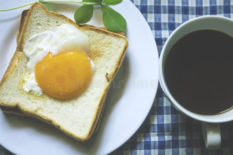 Fried egg on toast and black coffee in a glass. stock photo