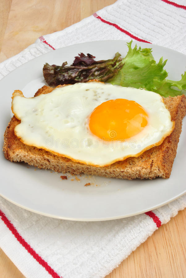 fried egg on toast bread with salad