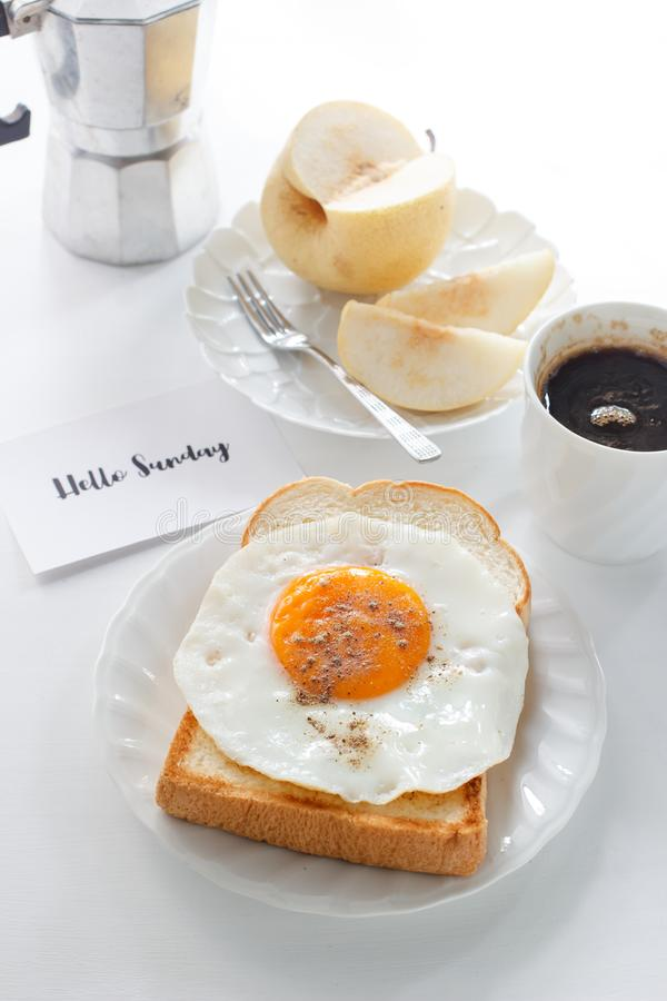 Fried egg on toast. Fruit, black coffee and text `Hello Sunday stock images