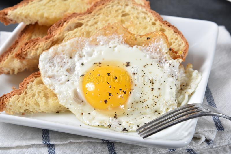 Fried egg on toast. A fried egg on hot, buttered gluten-free toast stock photos