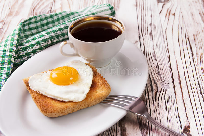 Fried egg with toast on a plate. Fried egg in the form of heart with toast on a plate stock images