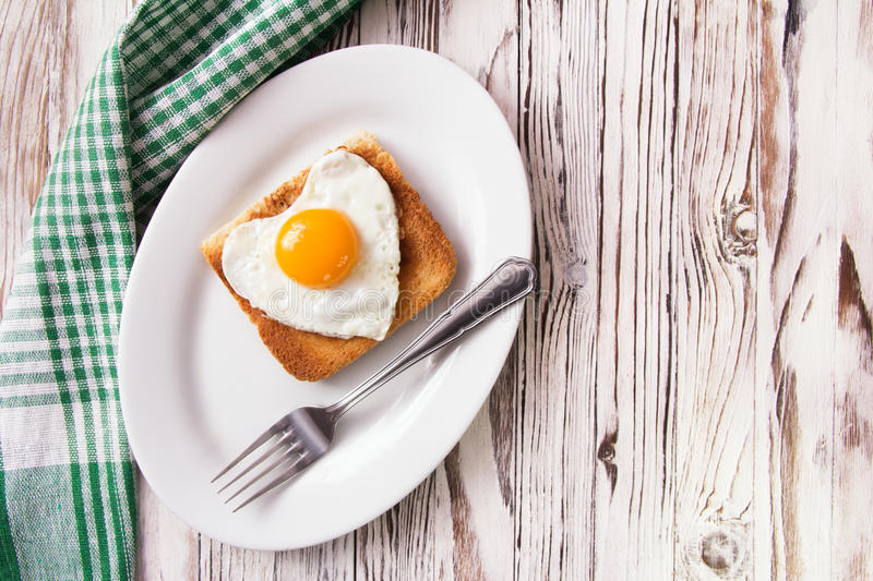 Fried egg with toast on a plate. Fried egg in the form of heart with toast on a plate royalty free stock photos