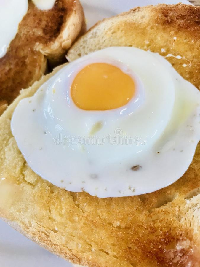 Fried egg on toast. Fried egg served on thick white buttered toast stock photo