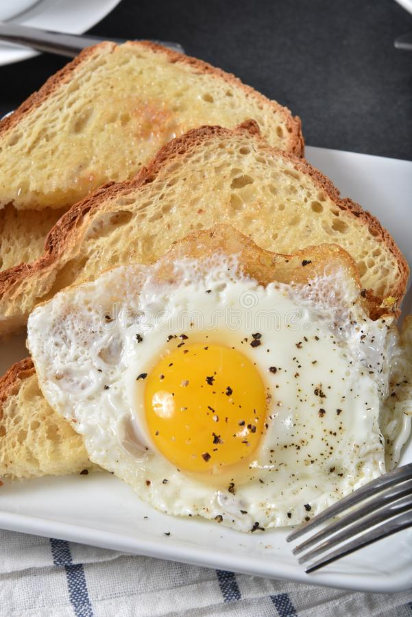 Fried egg on toast. Sunny side up fried egg on hot buttered gluten free toast, vertical view royalty free stock photos
