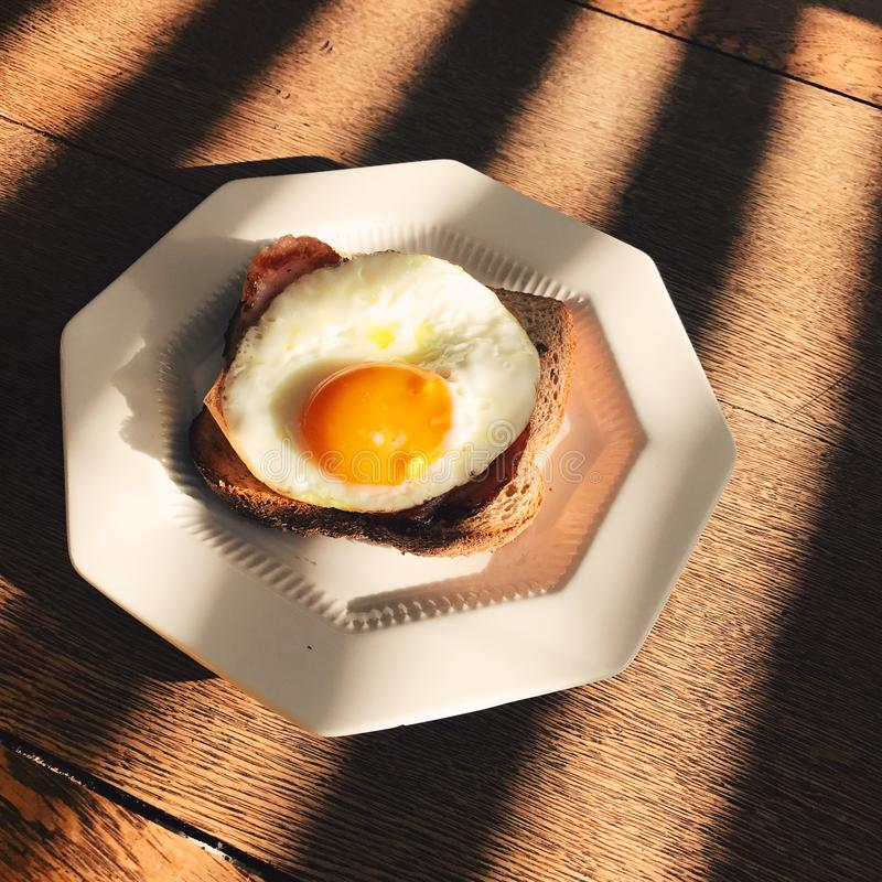 Fried egg on the toast. On the table royalty free stock image