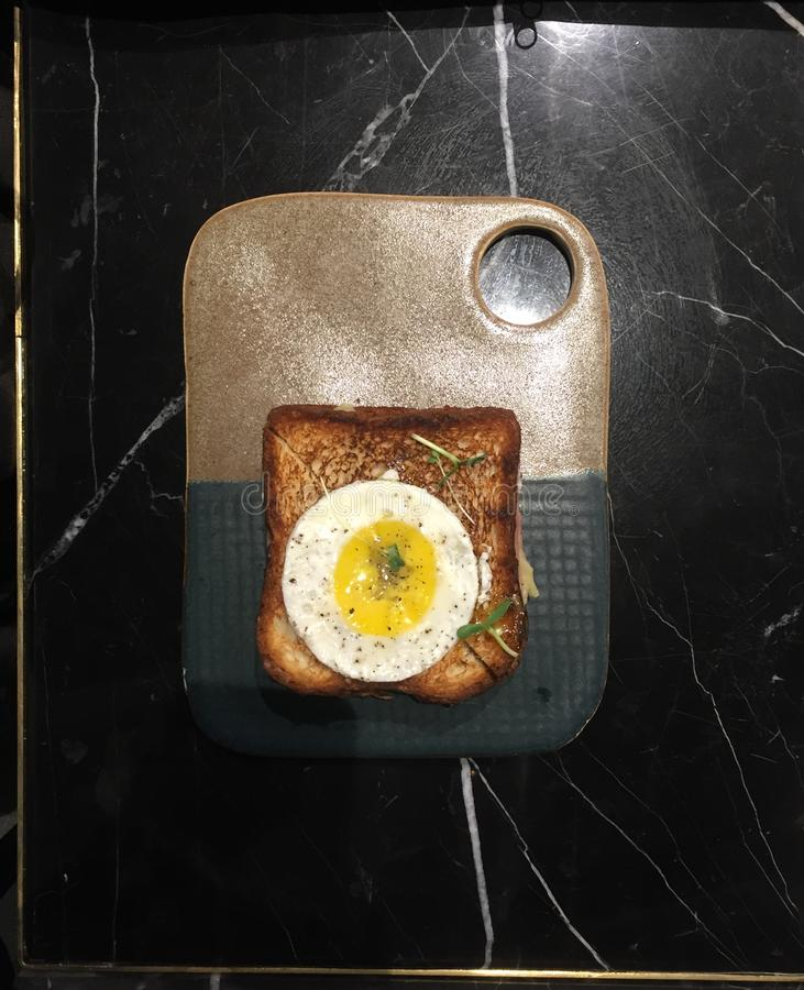 Fried Egg on Toast on a platter. Fried Egg on a well done toast on a ceramic platter royalty free stock images