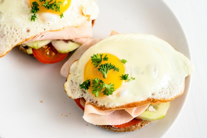 Fried egg on wholemeal bread roll with tomato, cucumber and cooked ham, healthy hearty breakfast on a white table, copy space, stock photography