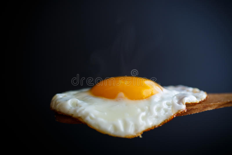 Fried egg with a wooden spoon. On a black background stock photography