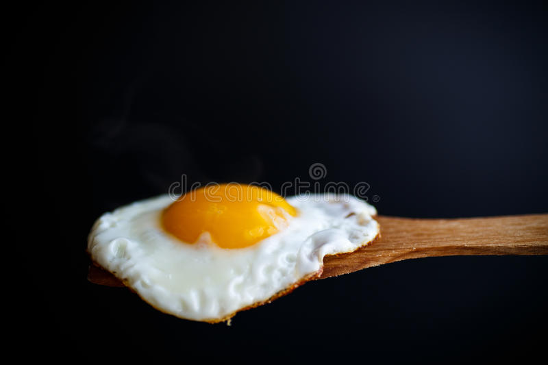 Fried egg with a wooden spoon. On a black background royalty free stock image