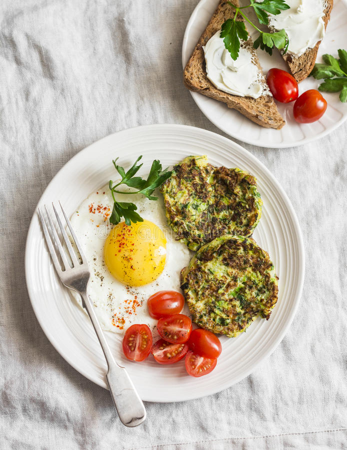 Fried egg, zucchini fritters and cream cheese sandwich - delicious breakfast, brunch or snack. On a light background stock images