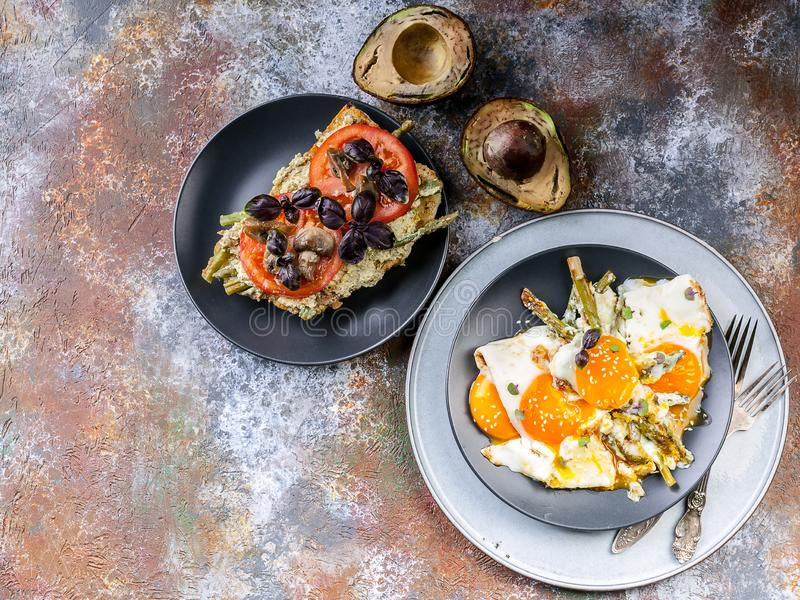 Fried eggs with asparagus, sandwich with pesto, tomatoes and mushrooms, ripe avocado. Tasty breakfast. Top view royalty free stock photo
