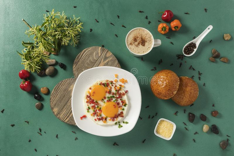 Fried eggs with bacon, red cucumber and green bread and chocolate on green background stock photos