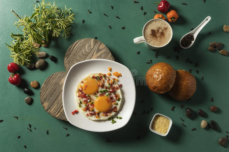 Fried eggs with bacon, red cucumber and green bread and chocolate on green background stock images