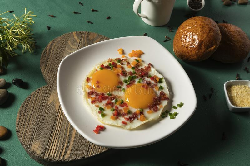 Fried eggs with bacon, red cucumber and green bread and chocolate on green background stock photography
