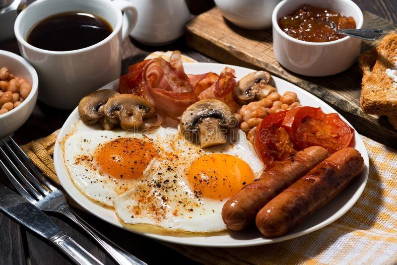 Fried eggs with bacon, sausages and vegetables for breakfast, closeup royalty free stock photos