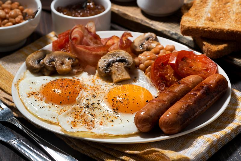 Fried eggs with bacon, sausages and vegetables royalty free stock photo