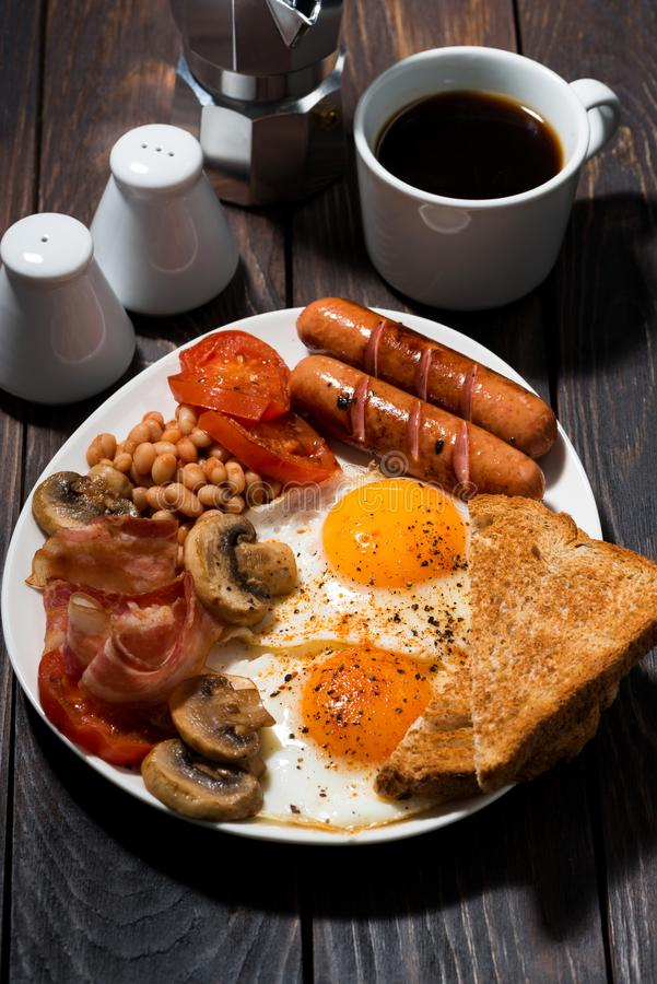 Fried eggs with bacon, sausages and vegetables on wooden table royalty free stock photo