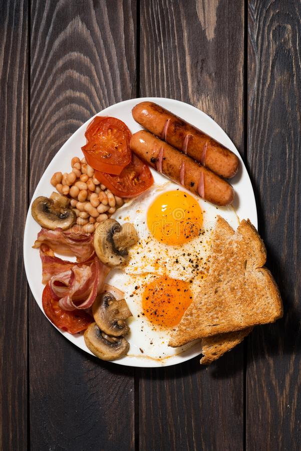 Fried eggs with bacon, sausages and vegetables on wooden table stock photos