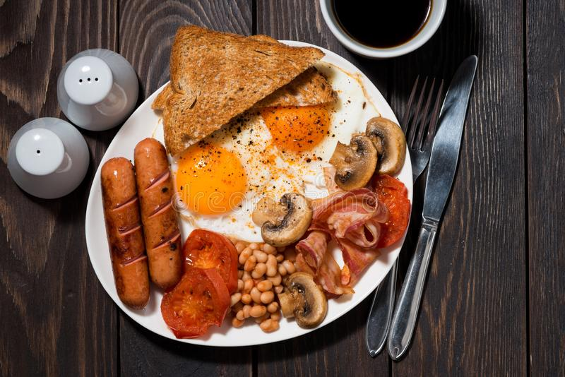 Fried eggs with bacon, sausages and vegetables on wooden table, top view closeup royalty free stock photos
