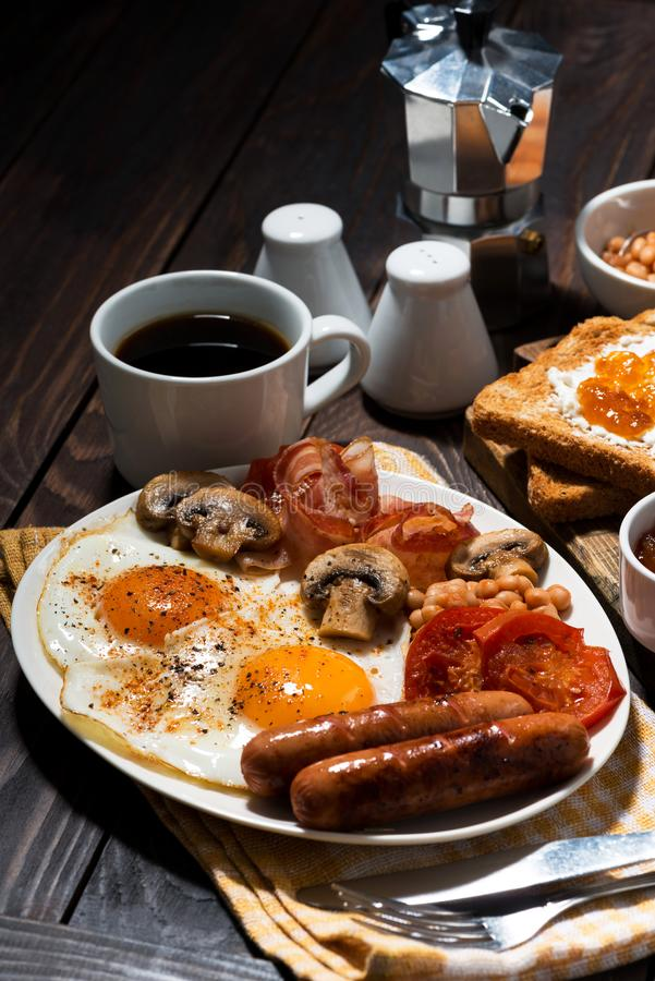 Fried eggs with bacon, sausages and vegetables on wooden table stock photo