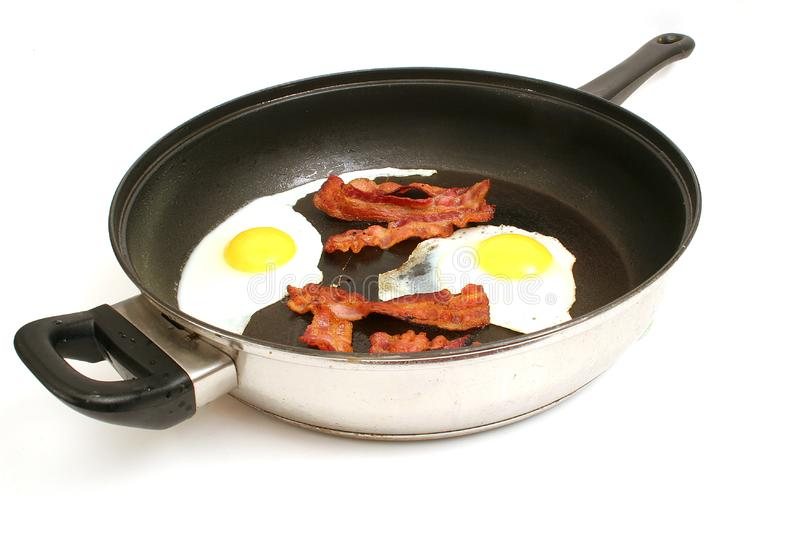 Fried eggs & bacon in skillet royalty free stock images