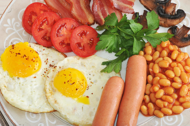 Fried eggs with bacon, tomatoes, beans, mushrooms and sausages. In a plate on wooden background stock photography