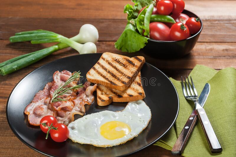 Fried eggs with bacon and vegetables on plate royalty free stock photography