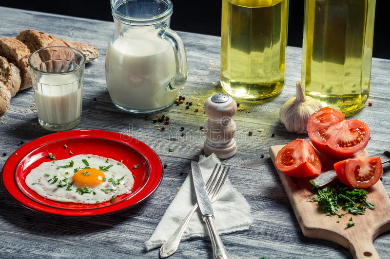 Fried eggs and bread for breakfast with vegetables royalty free stock photos