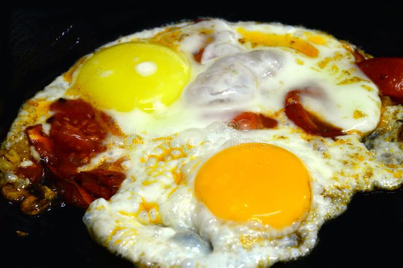 Fried eggs with colorful yolks and tomatoes. Fried on a black cast iron skillet. royalty free stock photography