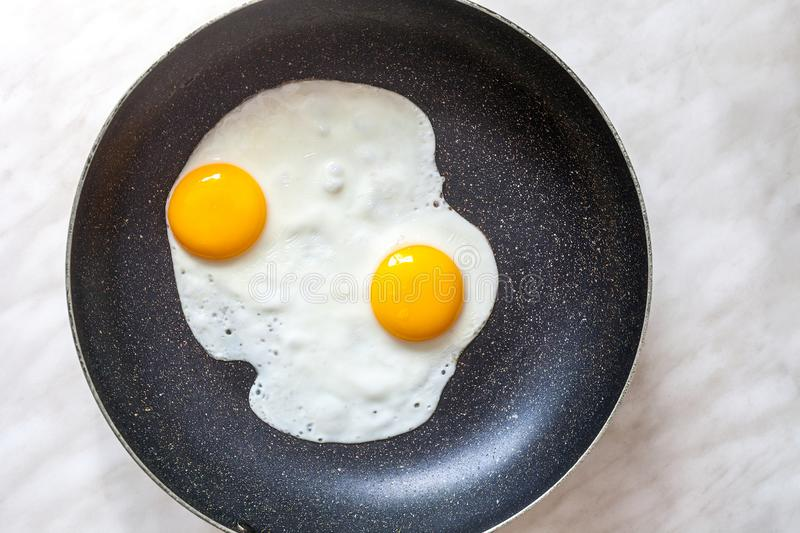 Fried eggs cooked in frying pan for breakfast, top view stock photos
