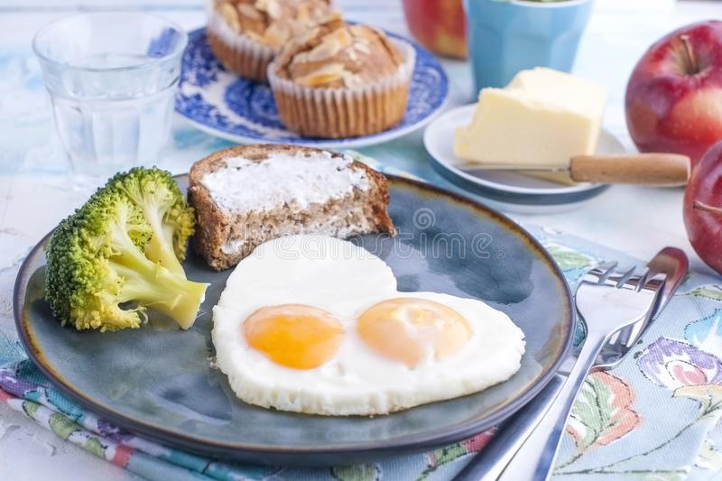 Fried eggs in the form of heart. On a dark plate with broccoli and toast. Blue cup with tea, butter for breakfast and cupcakes. On. A light colored background stock photo
