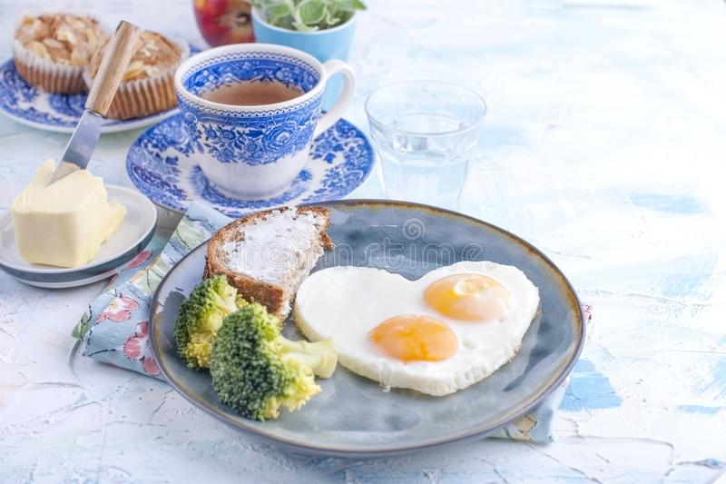 Fried eggs in the form of heart. On a dark plate with broccoli and toast. Blue cup with tea, butter for breakfast and cupcakes. On stock image