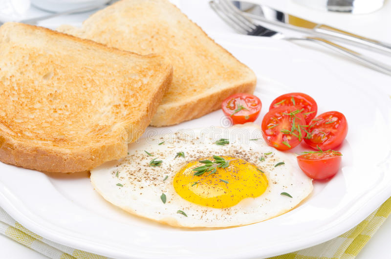 Fried eggs, fresh tomatoes and crunchy toast for breakfast. Closeup stock images