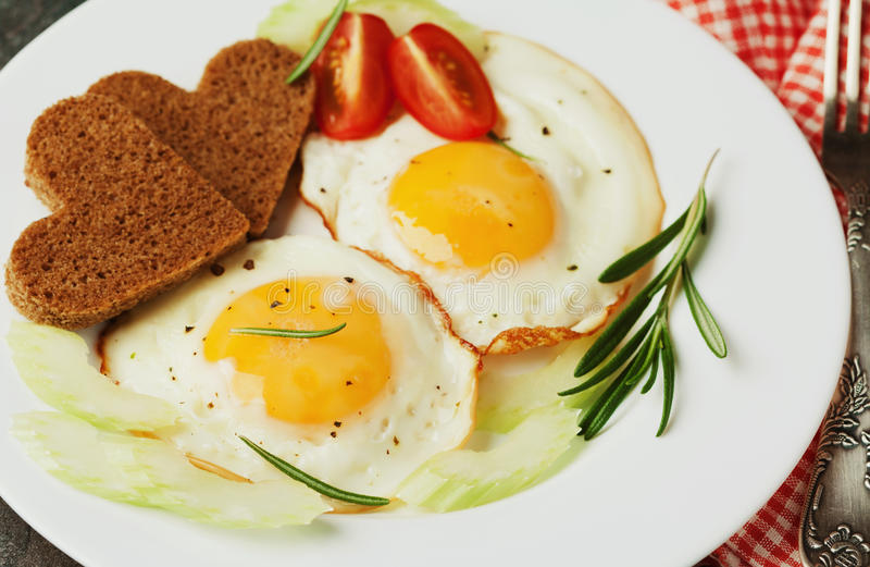 Fried eggs with fresh vegetables and toast in shape of heart on white plate. Delicious Breakfast stock photos