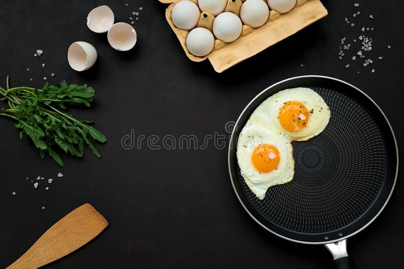 Fried eggs in frying pan with arugula leaves, salt and pepper for breakfast on black wooden background. Top view. Flat lay. Copy royalty free stock photo
