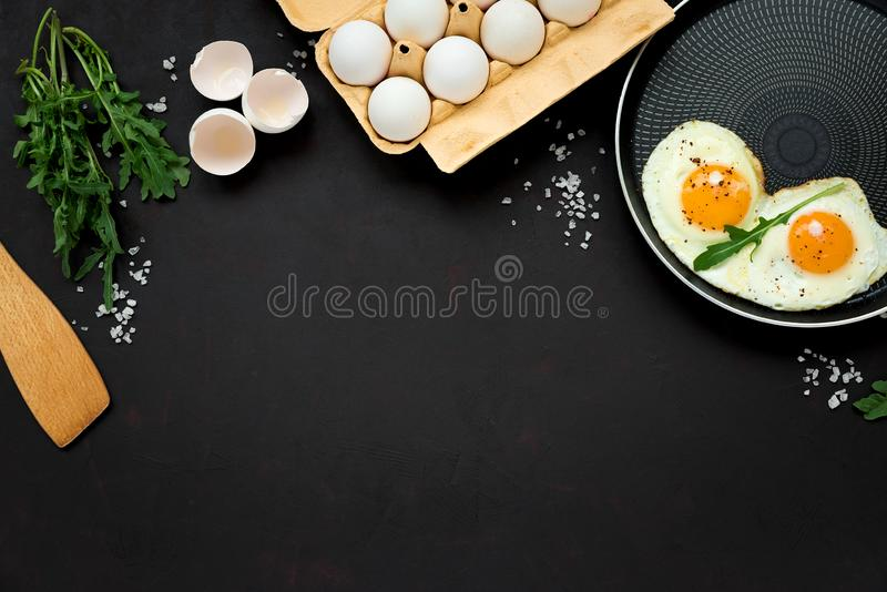 Fried eggs in frying pan with arugula leaves, salt and pepper for breakfast on black wooden background. Top view. Flat lay. Copy royalty free stock images