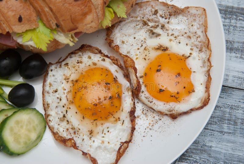 Fried Eggs inWhiteplatta med Sandwiche, svarta oliv och närbild för bästa sikt för gurka i lantlig stil på ett trä fotografering för bildbyråer