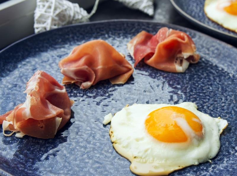 Fried eggs and jamon on a beautiful plate - a great light breakfast for a loved one. royalty free stock photography