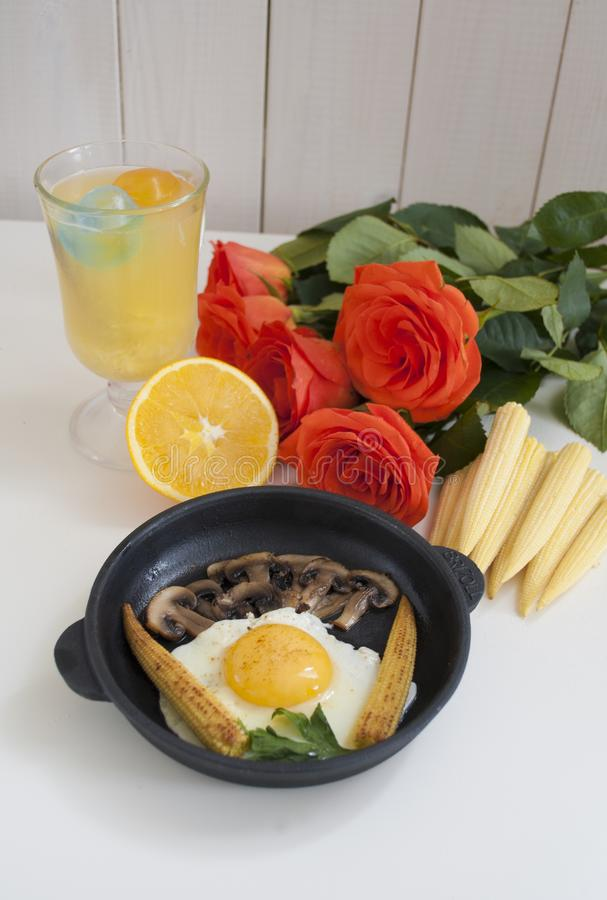 Fried eggs with mini corn and roses. Fried eggs with mini corn roses and orange royalty free stock image