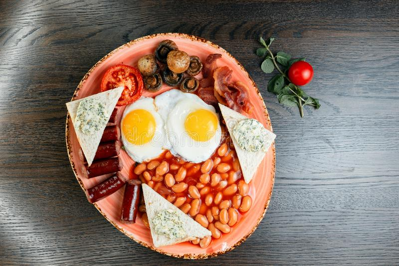Fried eggs, fried mushrooms, juicy sausages, fried bacon, toast with butter and pickled beans in tomato sauce on the table royalty free stock photo
