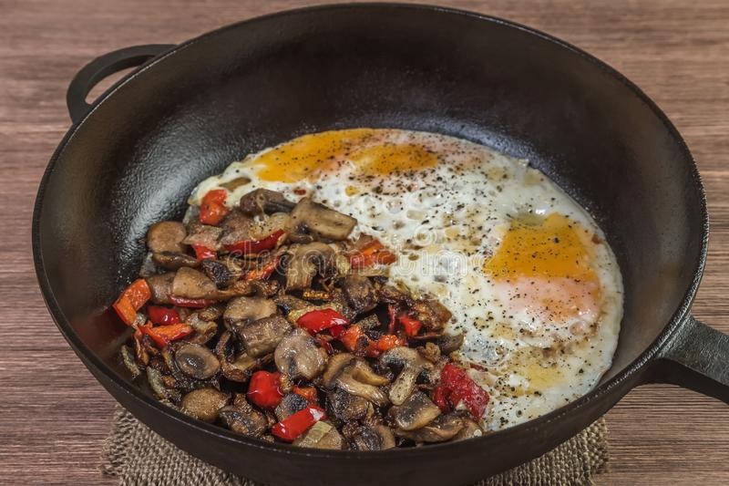 Fried eggs with mushrooms, onions and red pepper in a frying pan. Home-cooked food. Fried eggs with mushrooms, onions and red pepper in a frying pan. Homemade stock photo