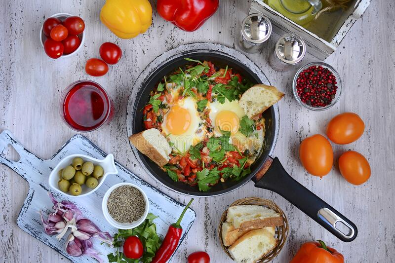 Fried eggs in a pan with vegetables and herbs, ripe tomatoes and peppers, zira, paprika, garlic, olives closeup. Delicious and. Nutritious breakfast. Top view royalty free stock photography