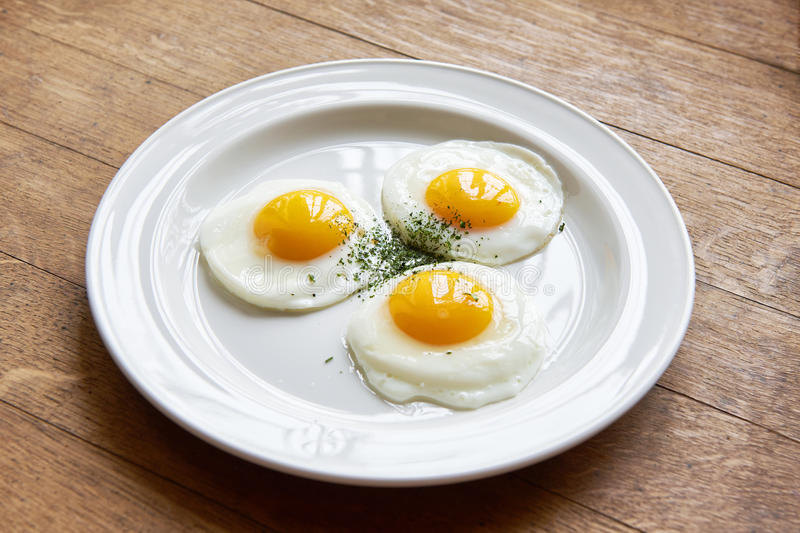 Fried eggs in plate on table. Fried eggs in a plate on the table stock images