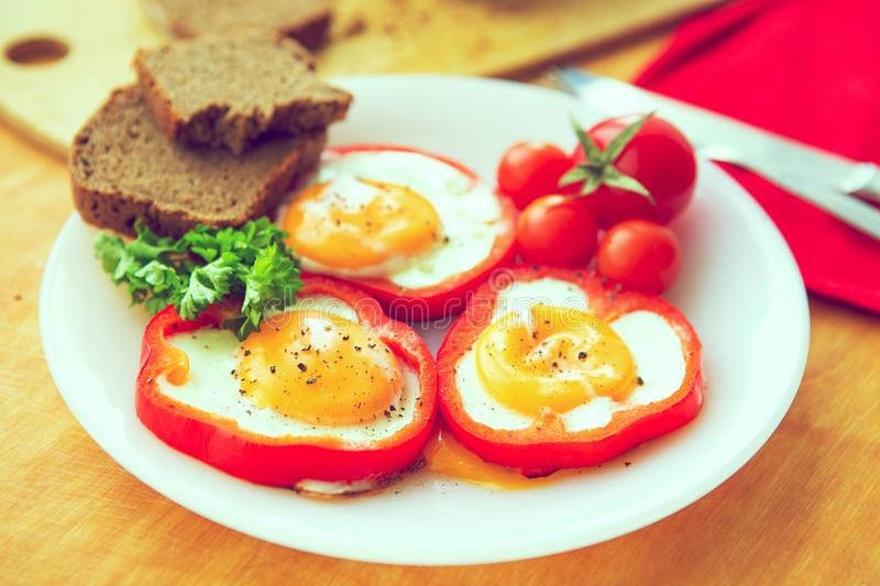 Fried eggs in red peppers in a plate close-up. horizontal view from above. Toned image.  royalty free stock image