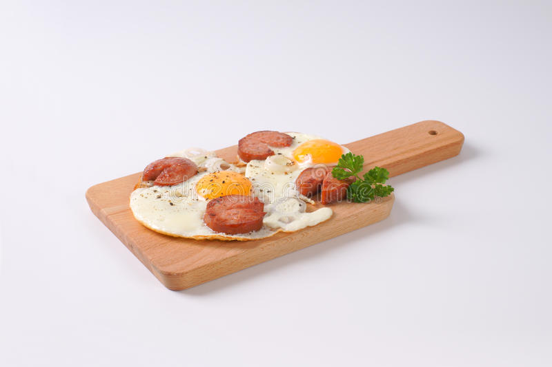 Fried eggs with sausage stock photos