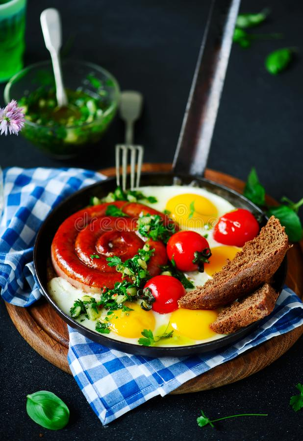 Fried eggs with sausages and green salsa stock photo